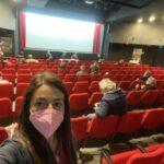 Selfie di donna con mascherina con alle spalle una sala teatrale.